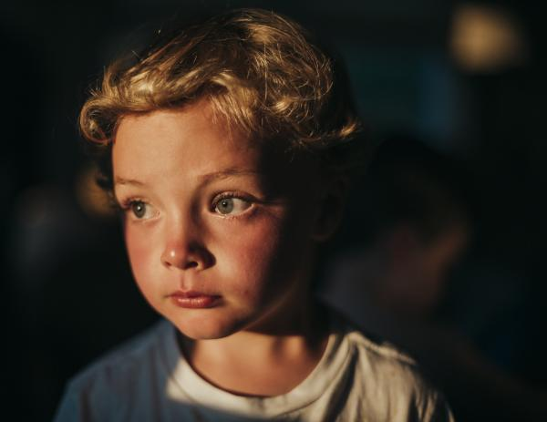Gannon Ryan, 5, stares out of the window as the sun sets on Nantucket Island, Mass. in mid July. This image was enhanced with Adobe Lightroom.