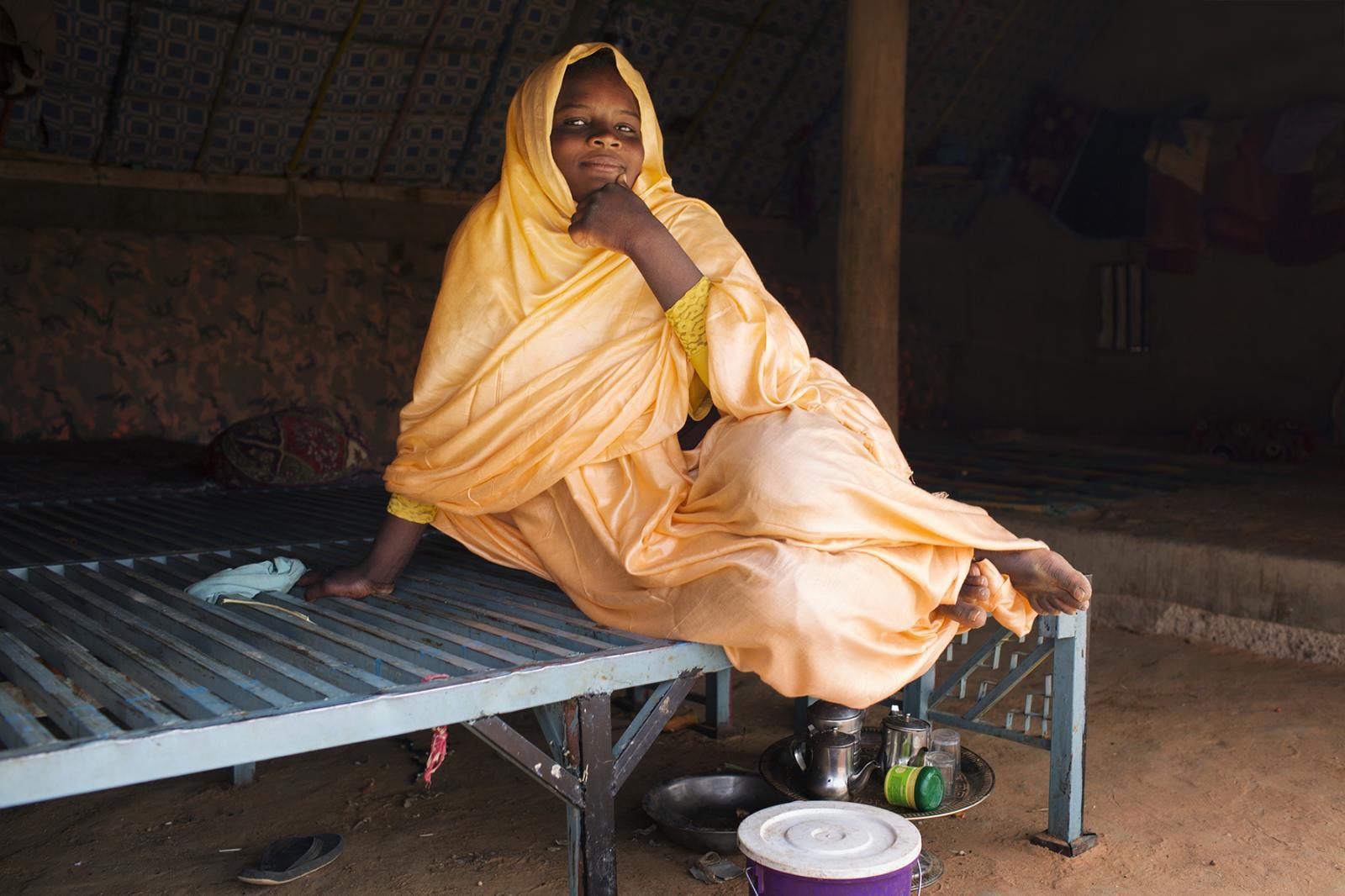 Une jeune fille, bénéficiaire de l'espace sûr de Nouamlein est assise sur un lit dans la maison familale. A young girl who is a beneficiary at Nouamlein's safe space is sitting on a bed in her family home.