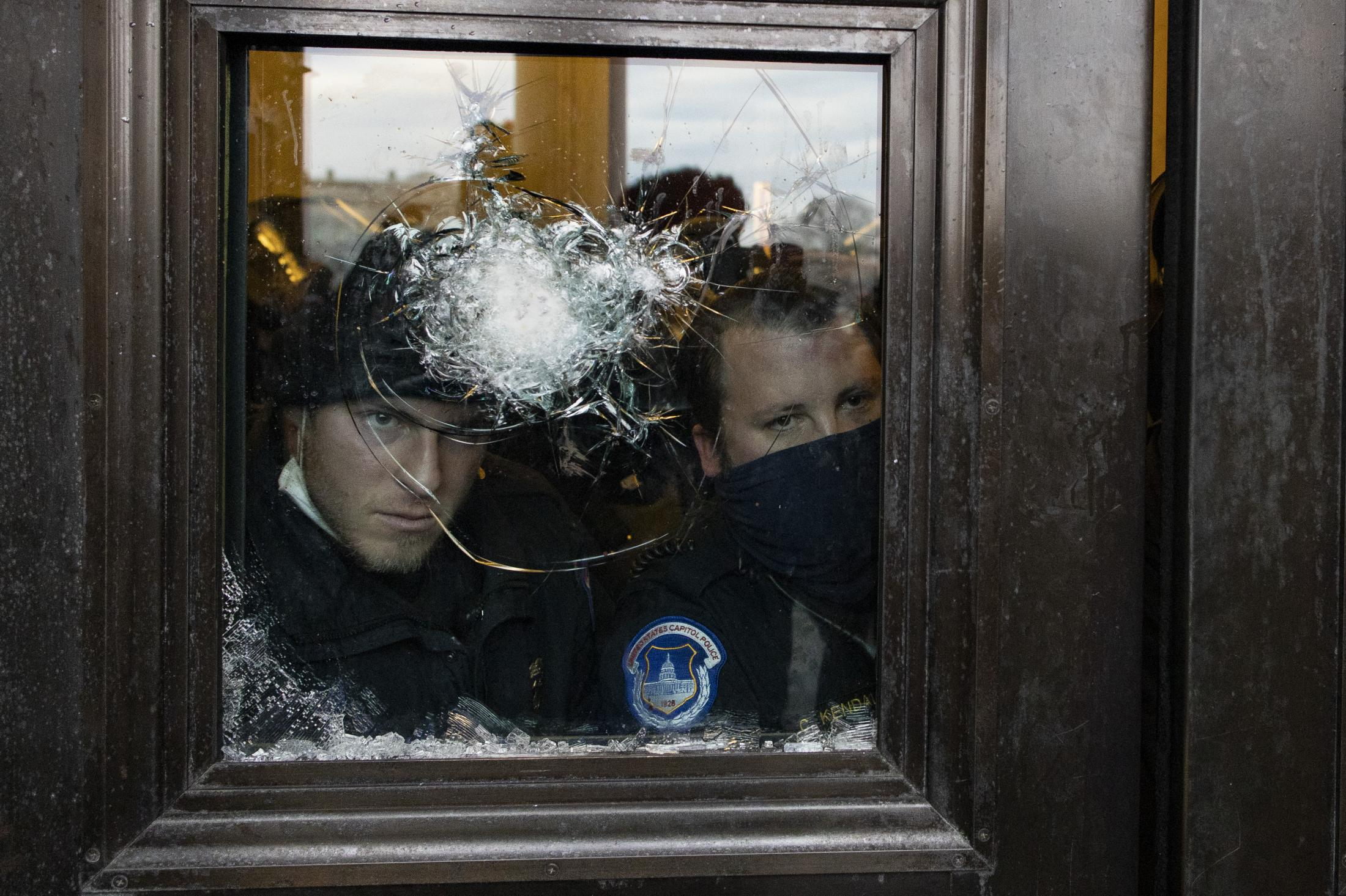 Members of the Capitol police look through a smashed window after they pushed supporters of US President Donald Trump outside of the Capitol building. January 6, 2021.