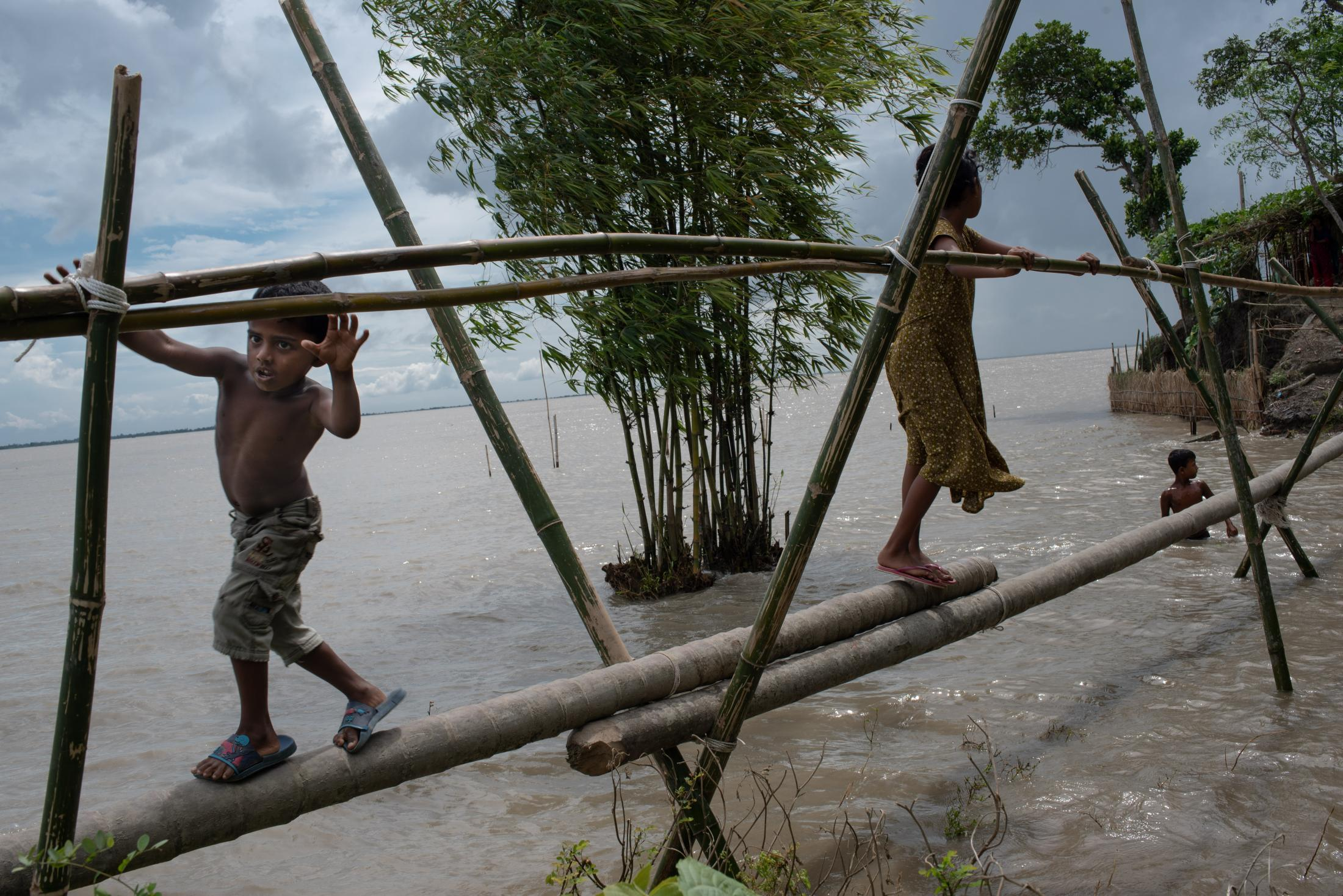 Children cross the pool over a recently formed canal due to the massive flooding of the Padma river at Manikganj.