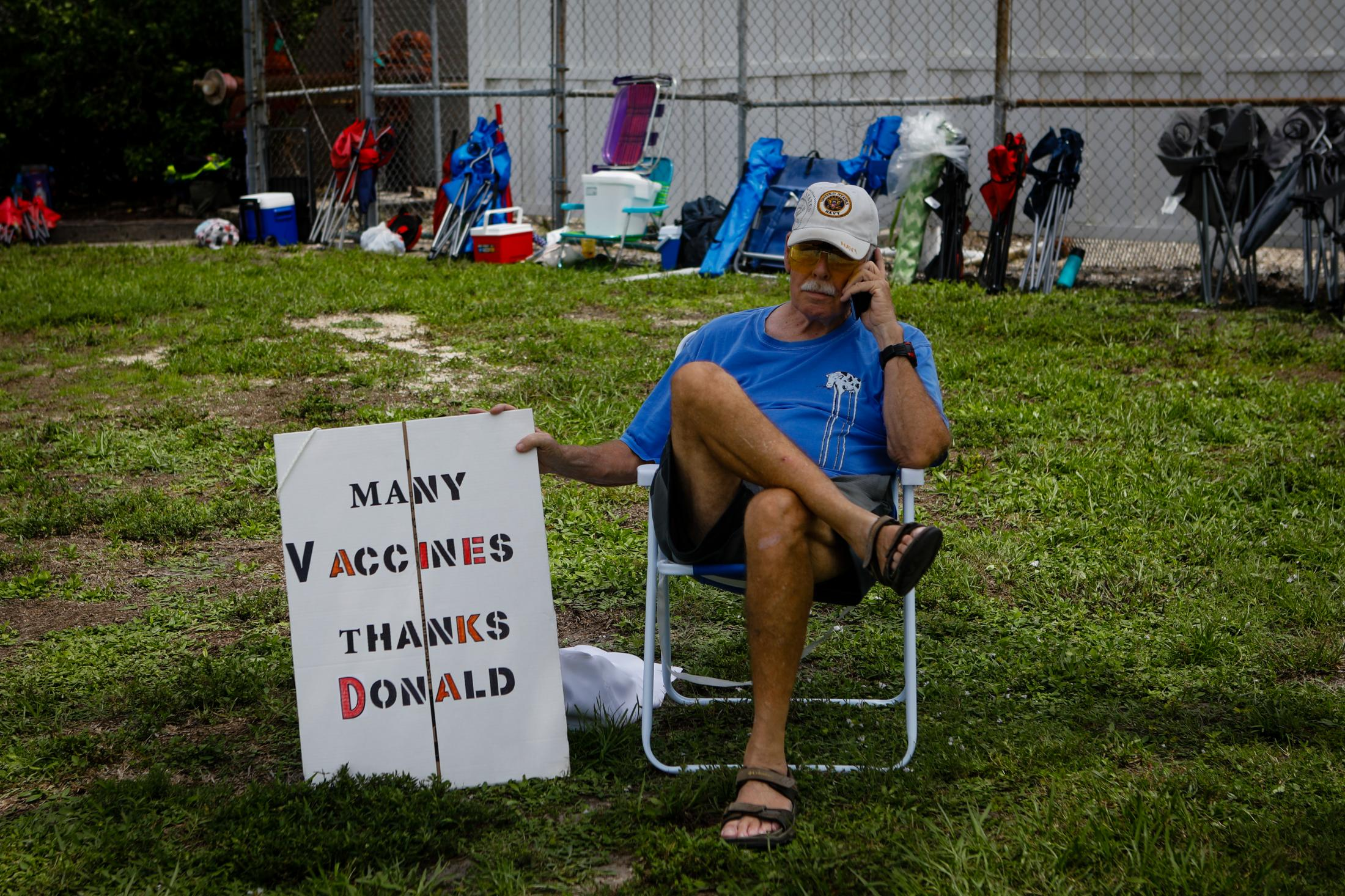 """SARASOTA, FL - JULY 03: A man holds a sign """"Many vaccines thanks Donald"""" as he waits for the arrival of former U.S. President Donald Trump to hold a rally on July 3, 2021 in Sarasota, Florida. Former U.S. President Donald J. Trump hold a major rally co-sponsored by the Republican Party of Florida and marks President Trump's further support of the MAGA agenda and accomplishments of his administration. (Photo by Eva Marie Uzcategui/Getty Images)"""