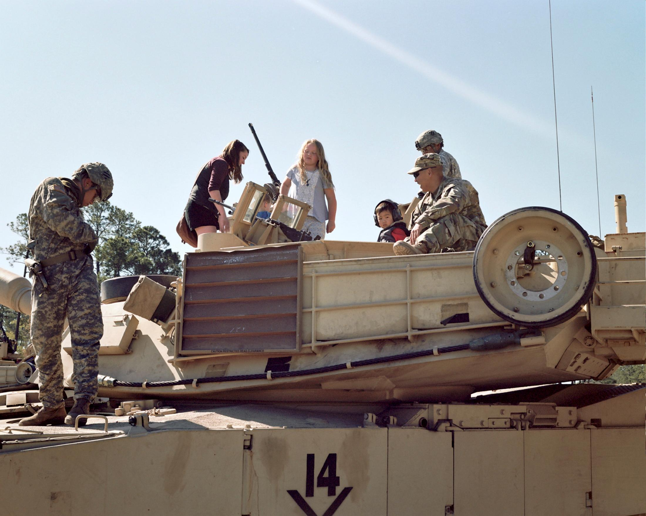 Military families move to new installations every two or three years. Often, spouses raise children alone during deployments. Here, military children climb onto a battle tank on Family Range Day in Fort Stewart, Georgia. PHOTOGRAPH BY ARIN YOON