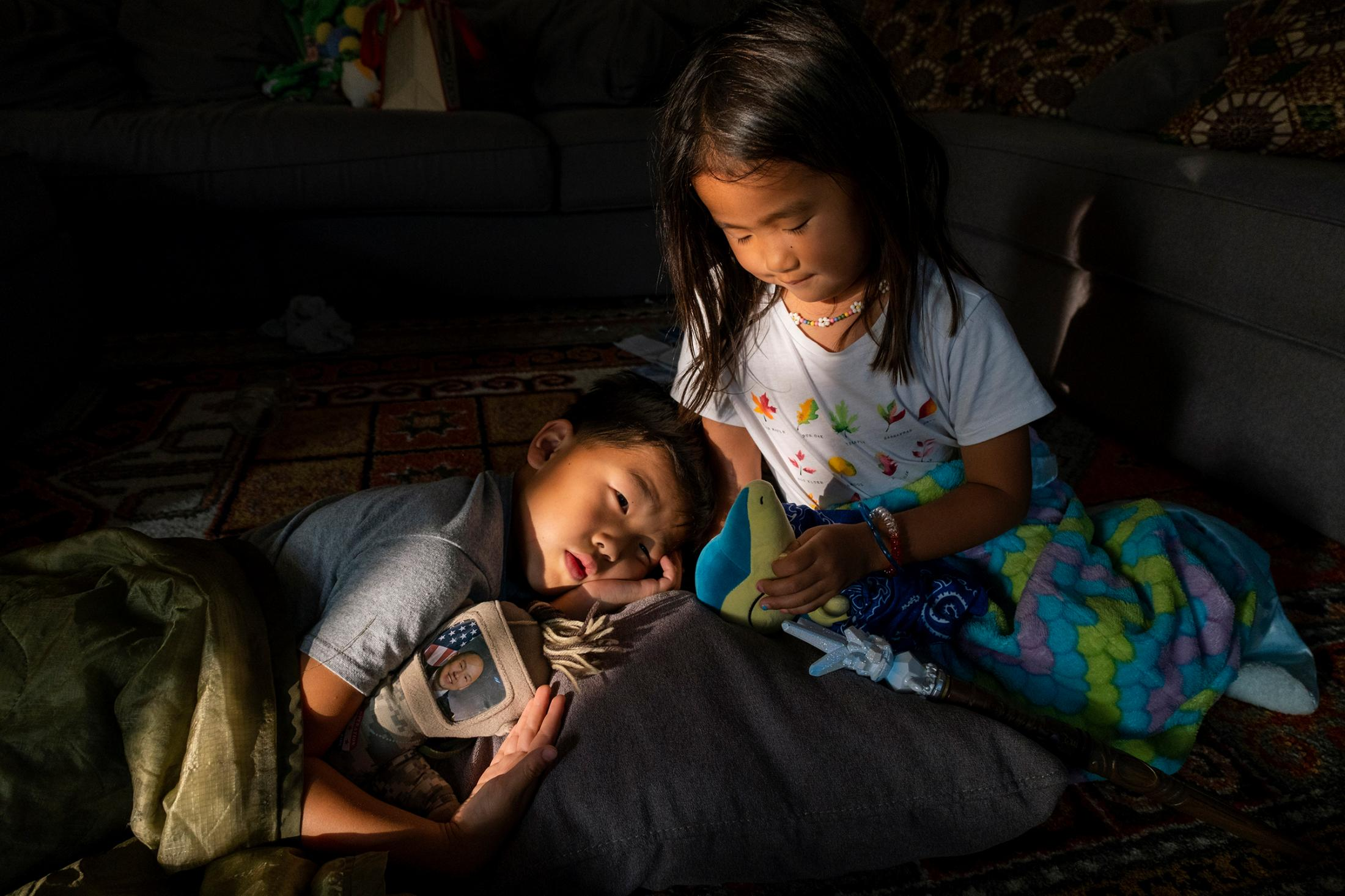 Teo holds a doll that has a photo of John inserted in a sleeve, while Mila takes care of her stuffed animal. PHOTOGRAPH BY ARIN YOON