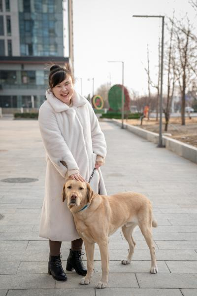 """Zhou Tong, 30, is from Zibo, Shandong. Her guide dog, Xiaojie, is an 8-year-old Labrador Retriever. Zhou applied for a guide dog in 2012, and met Xiaojie after three years of waiting. She's lucky compared to many other people with visual impairment in China. The high demand and low supply of guide dog in China has kept many people waiting for years to no avail. """"Xiaojie is the closest family to me. I can't spend 24/7 with my parents or my husband, but Xiaojie is always with me. I think our relationship is beyond kinship, friendship and romantic relationship.""""      Zhou works in a mobile gaming company that designs and develops games specifically for people with visual impairment. She works in PR writing and community engagement for the company. In her daily life, she relies on screen-reading technology to read to her what's on the screen of her cellphone and computer. If an APP is not optimized for screen-reading technology, she won't be able to use the APP properly. She thinks that APPs should be designed to be easy to use for both people with disabilities and people without. Only in this way can people with disabilities be fully integrated into the society.      周彤来自山东淄博,今年30岁。她的导盲犬小杰是一条8岁的拉布拉多犬。周彤在2012年申请导盲犬,等待了3年后终于见到了小杰。和中国许多其他视障人相比,周彤是十分幸运的。中国的导盲犬供不应求,很多人等待多年都无法申请到。""""小杰是我最亲的人,因为不管是父母也好,我老公也好,他都没有办法跟我24小时待在一起,但是小杰是24小时在陪着我。所以我们的关系可能超越所有的亲情、友情、爱情。""""周彤说。     周彤在一家专为视障人做手机游戏的公司做PR和社群运营。在她的日常生活中,她依靠读屏技术使用手机和电脑。如果一个软件没有为读屏技术做过优化,她就无法正常使用。她认为APP应该同时对残障和非残障都使用友好,这样才能促进社会的残健融合。"""
