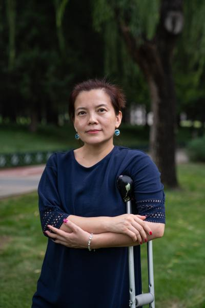 """Zhao Aihong, 43, works in sales at an insurance company. She lives with her mother in Beijing, in order to take care of her.      She thinks of herself as a perfectionist at work. Some of her clients have disabilities as well, and Zhao serves them by recommending the most suitable insurance packages. """"I want to help as many people as possible, but I don't have the financial capacity to do so. It's very rewarding to know the insurance product I select for my clients turn out to be useful and help them in a difficult situation,"""" Zhao said. Knowing that many insurance policies work against the favor of people with disabilities, she hopes there will be an insurance product in the future that caters to the need of people with disabilities.      Zhao loves to travel and has travelled all over China. When she was in her 20s, she would go hiking in the mountains with her friends regularly. Although she knows the health of her knees is deteriorating faster than people without disabilities, she says, """"I want to travel as much as possible while I still can.""""      赵爱红今年43岁,是保险公司的销售。为了照顾妈妈,她和妈妈一起住在北京。      在工作上,赵爱红是一个完美主义者。她的一些客户也有残障,赵爱红尽最大努力为他们推荐合适的保险产品。她说:""""我想多帮助一些人,但我可能没有那么多钱帮助每一个人。保险给客户带去的是保障,而不是说我特别想帮别人的时候我没有办法。""""很多有残障的人在投保时会遇到困难,对此,赵爱红希望将来会有专门针对残障人群需求的保险。      赵爱红热爱旅游,全国各地都走遍了。她在20多岁时,经常和朋友们一起去爬山。因为手术和关节磨损,她要比其他人更早地面对身体的局限。但她仍然说:""""趁着我现在走得动的时候,我就想多走走。  """""""