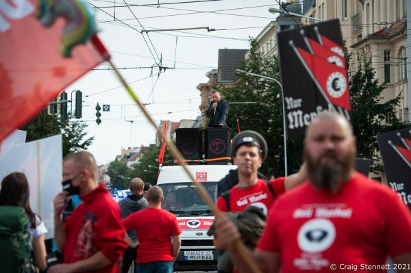 HALLE, GERMANY - OCTOBER 3: Elements of the 'Querdenken' movement, 'Anti-Antifa Germany' and other far right supporters and conspiracy theorists join together to demonstrate and march. The event held on The Day of German Unity was organised by Sven Liebich-seen leading the demonstration from a podium aboard a lorry- in Halle (Saale). Outgoing German Chancellor Angela Merkel attends celebrations to mark Unity Day on October 3, 2021 in Halle, Germany. Unity Day marks the reunification of Germany in 1990 following its division between West Germany and East Germany during the Cold War. (Photo by Craig Stennett/Getty Images)