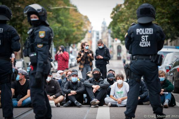 HALLE, GERMANY - OCTOBER 3: Protesters block a street in the city centre as part of a counter demonstration held by 'Halle against the Right' against supporters of the 'Querdenken' movement and members of the far-right who were marching and protesting against Angela Merkel, under the loose and contradictory title of 'Geil Merkel,' on German Unity Day on October 3, 2021 in Halle, Germany. Merkel is in Halle today to attend Unity Day celebrations. Unity Day marks the reunification of Germany in 1990 following its division between West Germany and East Germany during the Cold War. (Photo by Craig Stennett/Getty Images)