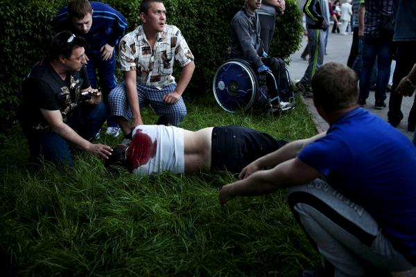 People stand next to the body of a man who supports Russia in the city of Krasnoarmeisk, Ukrainian national guardsmen opened fire on a crowd outside a town hall, trying to stop the May 11 referendum from taking place in the village.