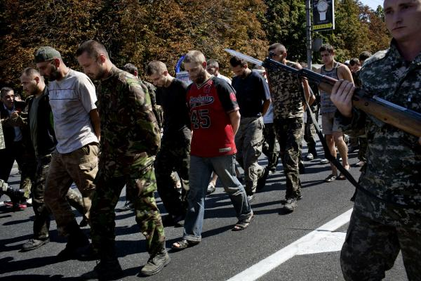 A Donetsk people militia man, escorts captured Ukrainian army prisoners, in the central square of Donetsk, eastern Ukraine.