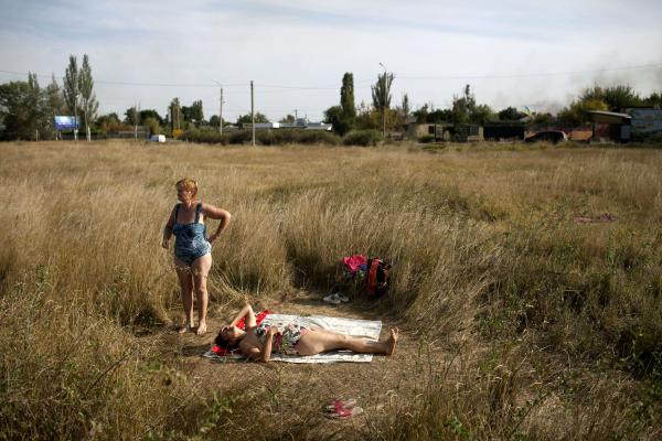 Residents of Slovyanks, a city that was under control of Donetsk people militia, and was captured by the UA army, taking a rest during a hot summer day.