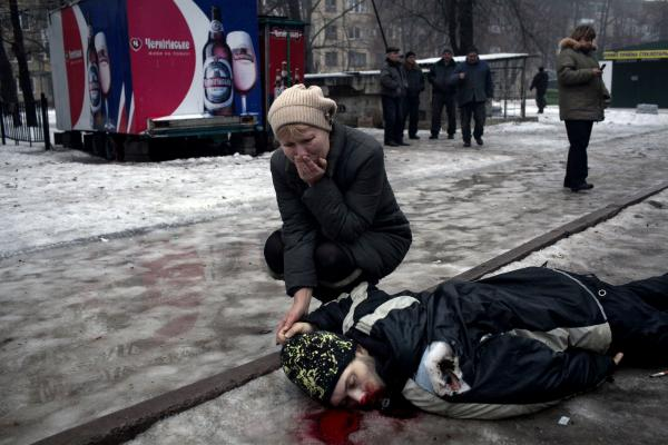 A mother holds her son's hand while mourning his death after a grad rocket attack in a residential area of Donetsk city.
