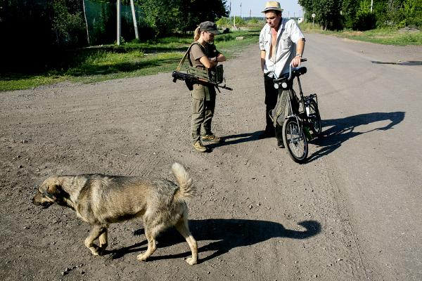 A Ukrainian soldier and a civilian, talking near the Karlivka village checkpoint.The village is located approximately 17 km west of Donetsk city.