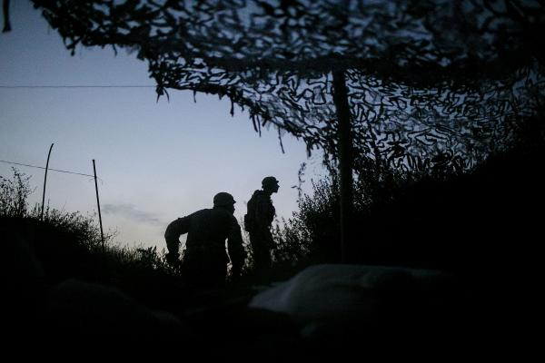 Ukraine army soldiers, looking towards LPR (Luhansk People's Republic) positions, as machine-gun fire echos around other UA army positions close by. near Troitske village, Luhansk region.