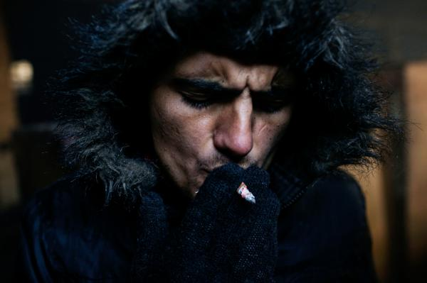 A young refuge smokes a cigarette, inside a warehouse located at the back side of Belgrade train station.