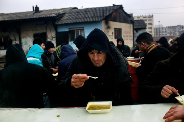Refugees eating warm food, distributed by volunteers every day at 13:00, near the abandoned warehouse where they live in.