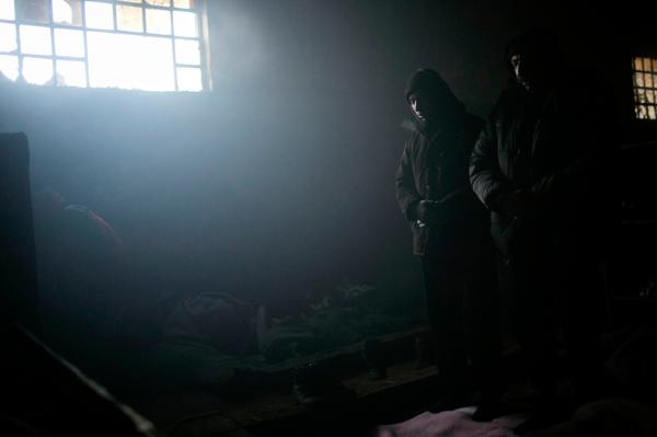 Two refugees praying inside a warehouse, at the backside of Belgrade train station.