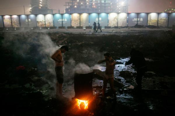 Refugees washing themselves during a cold night, at the back side of Belgrade train station.