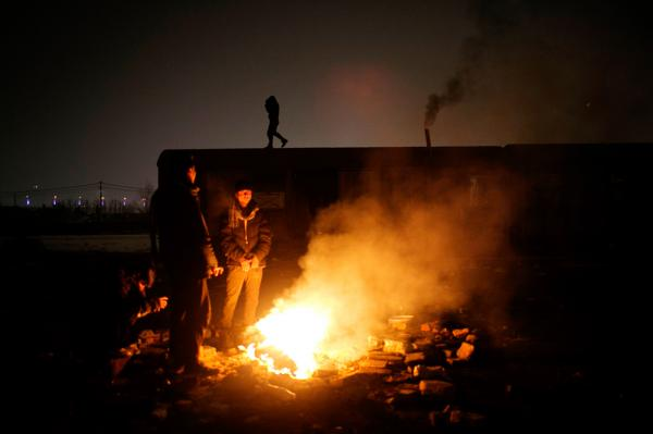 Refugees warming themselves by a fire, they sleep in a train cart at the backside of Belgrade train station.
