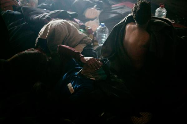 Two young refugees waking up coughing from smoke made by fire that kept them and other refugees warm during a cold night, at the back side of belgrade train station.