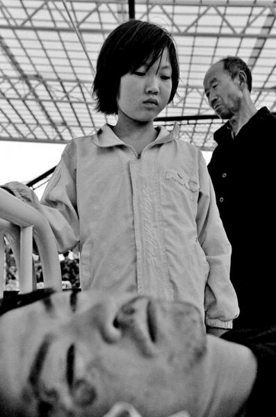 A daughter watches her father , who was injured during the quake, at a field hospital . Mianzhu town, Sichuan province.