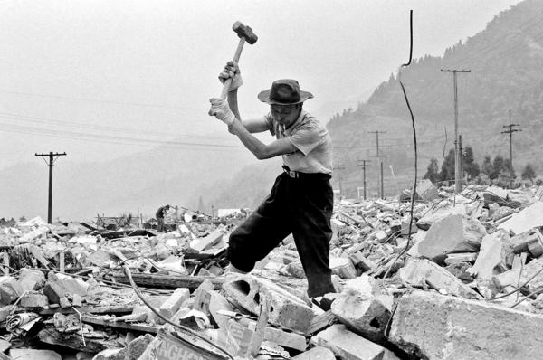 A man looking for iron in his destroyed house, in order to sell it, Hongbay village, Sichuan province.