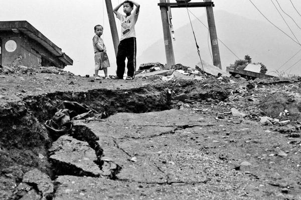 Children standing by their destroyed home, Hongbay town.