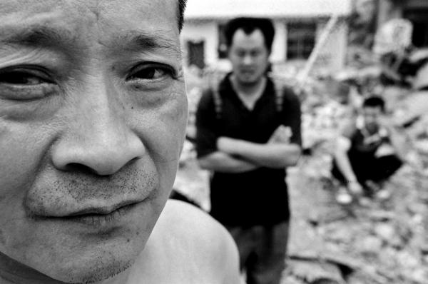 Survivors at their destroyed home, at the town of Legiu, Beichuan county.