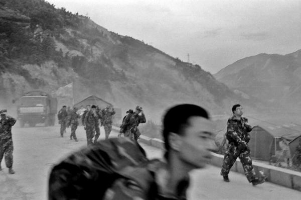 Chinese soldiers walking back to their camp after finishing one of many shifts of clearing rubble and searching for survivors at the town of Yingxiu.