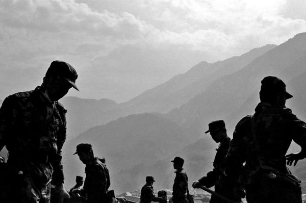 Soldiers clearing rubble from a road that was blocked by one of the many quake landslides. Yingxiu, Sichuan province.