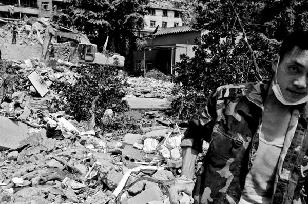A quake survivor searching the rubbles of his destroyed home for anything that was left intact. Yingxiu town.