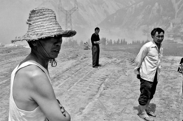 Survivors of the quake from Yingxiu, looking at their destroyed town being blown up by soldiers in order to make clearing of rubble easier.