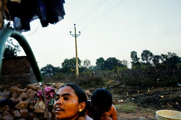 Women taking bath at the living quarters of steel plant workers (mainly their husbands) in the village of Tarimal, that borders one of the main sponge plant, in Raigarh district, Chhatisgrah, India.