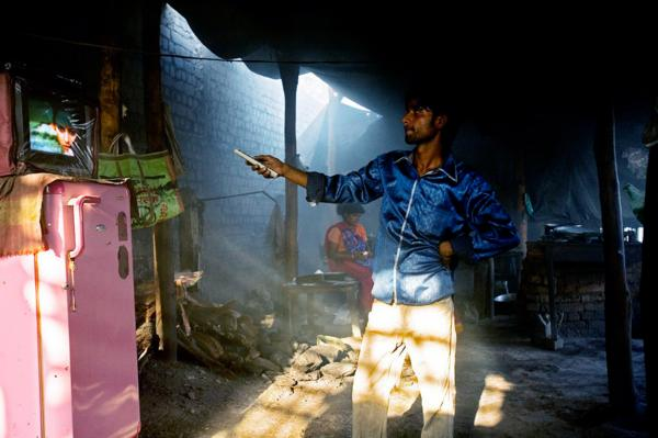 A truck stop owner, adjusts the TV in his shop, for drivers who transport steel from the village of Jamgon, Chhatisgrah.
