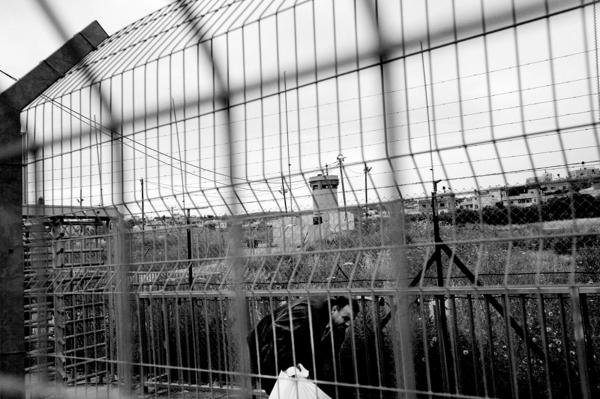 A Palestinian man crosses over, through an Israeli checkpoint, from the West Bank to Israel, while reservists keep watch.