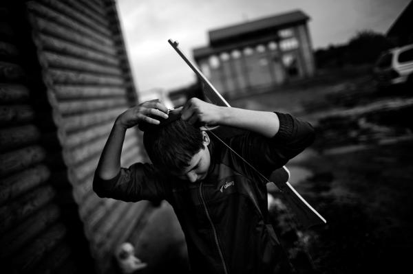 Kyryl (age 15), a young Jewish IDP from Luhansk, adjusts his Kippa on his head, while playing with a wooden AK-47 outside of his living quarters in Anatevka. Kippa is a brimless cap, worn by Jews to fulfill the customary requirement held by orthodox halachic authorities.