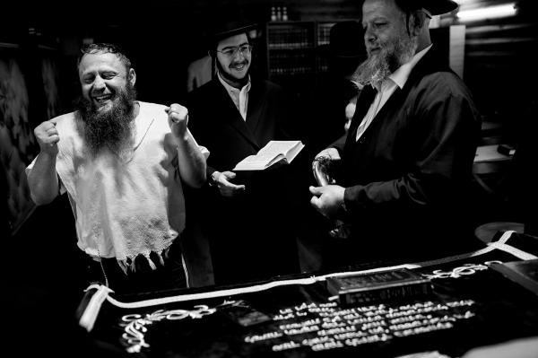 A Member of the Jewish community of Kiev (L) celebrating inside the village synagogue with two Orthodox Jews who came to visit Anatevka from Israel.
