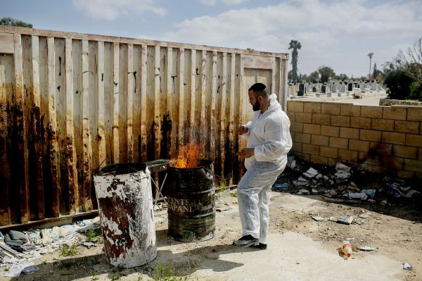 A gravedigger burns cloths that he used while removing a body of a man who passed away from Covid-19. Beer-Sheva cemetery.