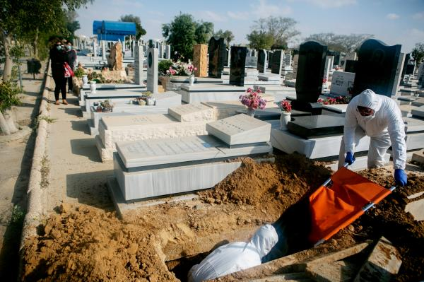 Gravediggers putting the body of Yaffa Nagar (90) into her grave. she passed away from Covid-19 during the first 2 months of the pandemic. Beer-Sheva cemetery.