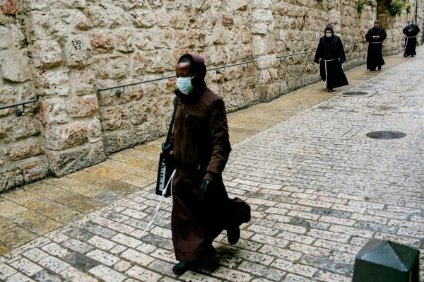 Good Friday procession taking place in Jerusalem without any participants other than monks.