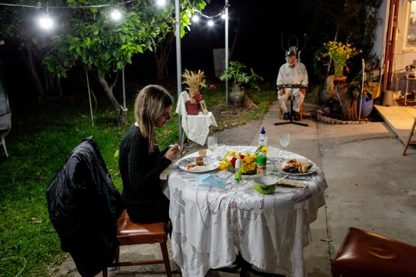 A daughter and her father sitting for evening meal, keeping a safe distance, during the first month of the pandemic. Northern Israel.