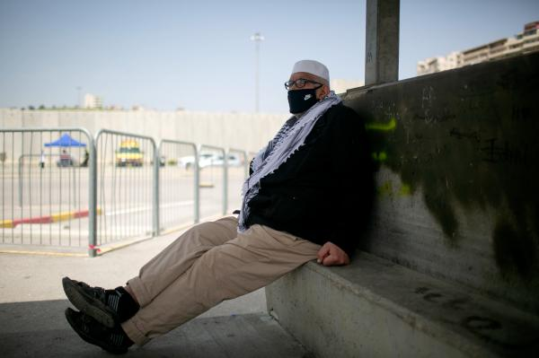 A Palestinian man, waiting to be tested for Covid-19, at the entrance to Shuafat refugee camp. East Jerusalem.