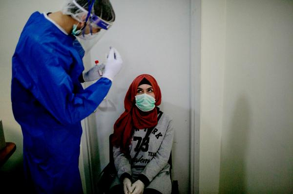A Palestinian girl, waiting to be tested for Covid-19, at a clinic in Shuafat refugee camp. East Jerusalem.
