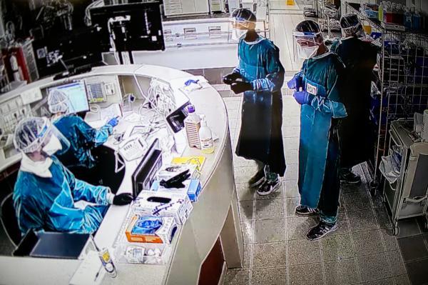 Doctors and nurse inside the emergency Covid-19 unit, seen through video screens outside the unit itself. Ichilov hopsital, Tel-Aviv.
