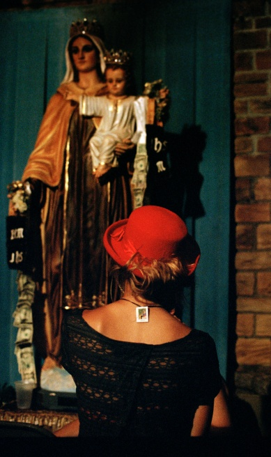 A woman prays in front of the statue of Our Lady of Mount Carmel.