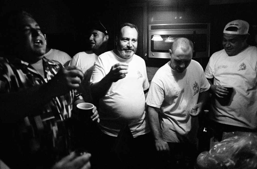 The men of the community take a break at one of their homes and make a toast during the Questua.