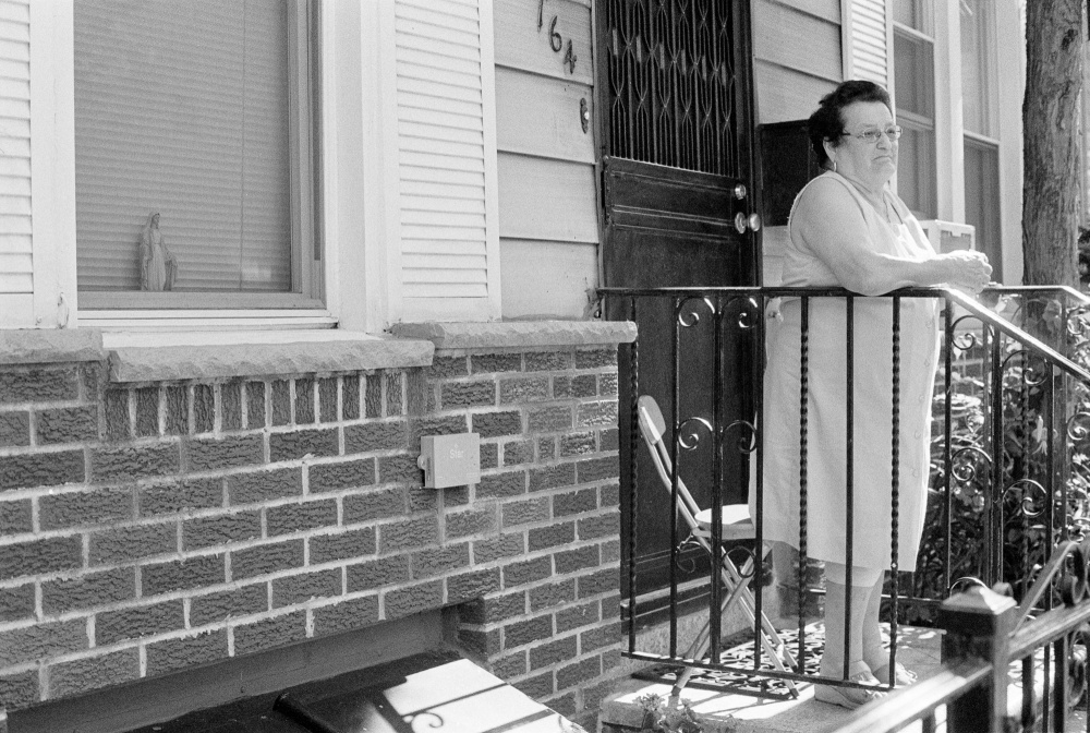 A woman watches the procession from her stoop.