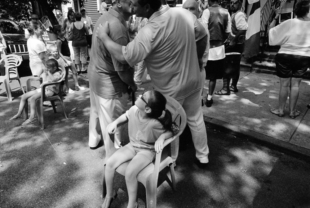 A young girl sits in the street during the Giglio Feast.