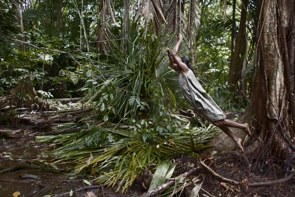 "Many warao consider the spirits or ""jebus"" who live in the forest are the cause of their fate. Despite the strong influence of missions among them their ancient beliefs still rule their world view on a very primary level. A transgender jumps over a puddle held to a vine."